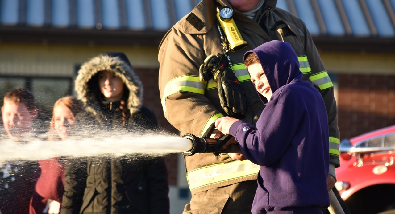 A middle school student participates in the local fire department's fire safety activities.