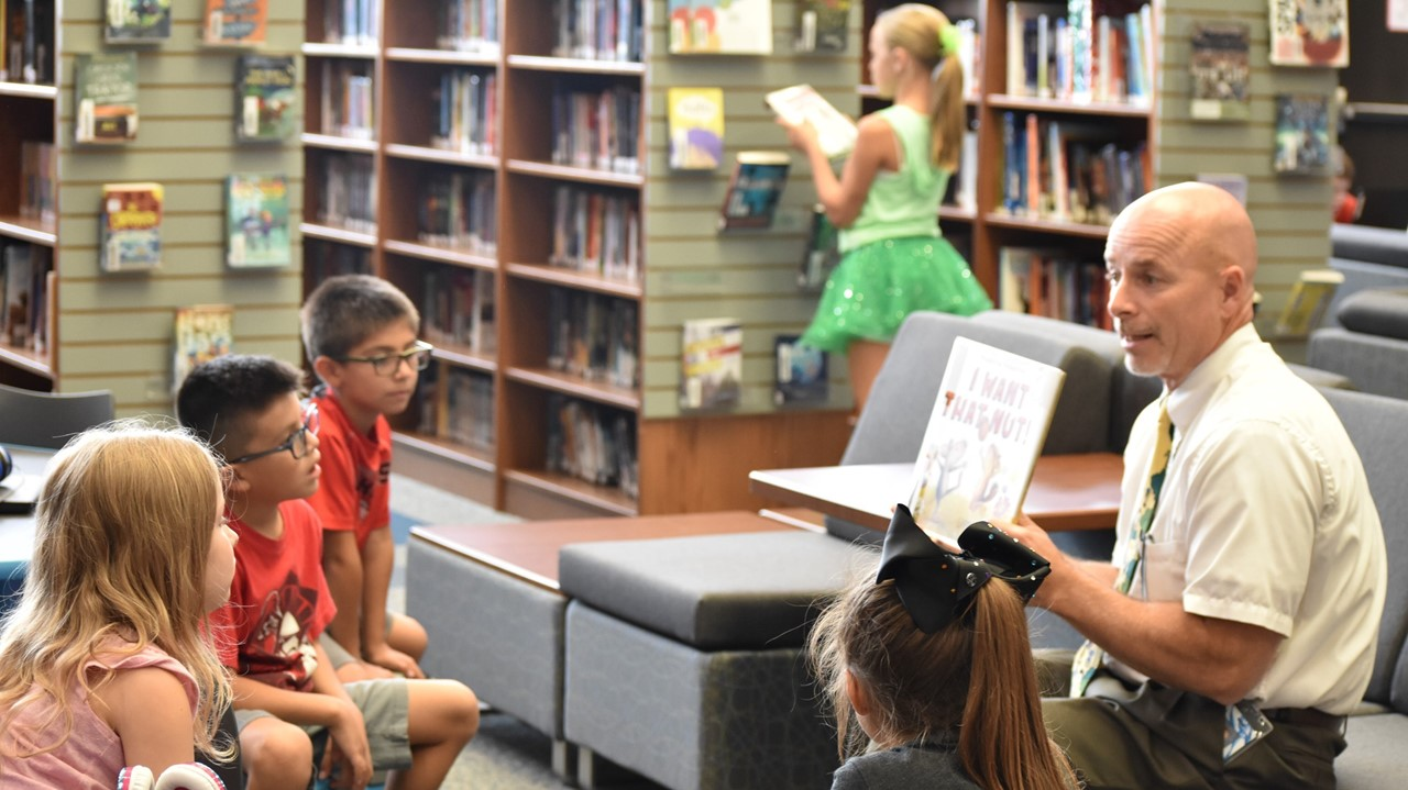 Superintendent Dr. Miller reads a library book purchased by the Rotary to elementary students.