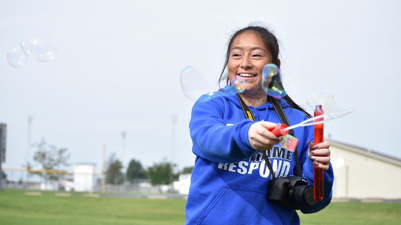 A yearbook student blows bubbles as classmates practice using aperture settings on their cameras.