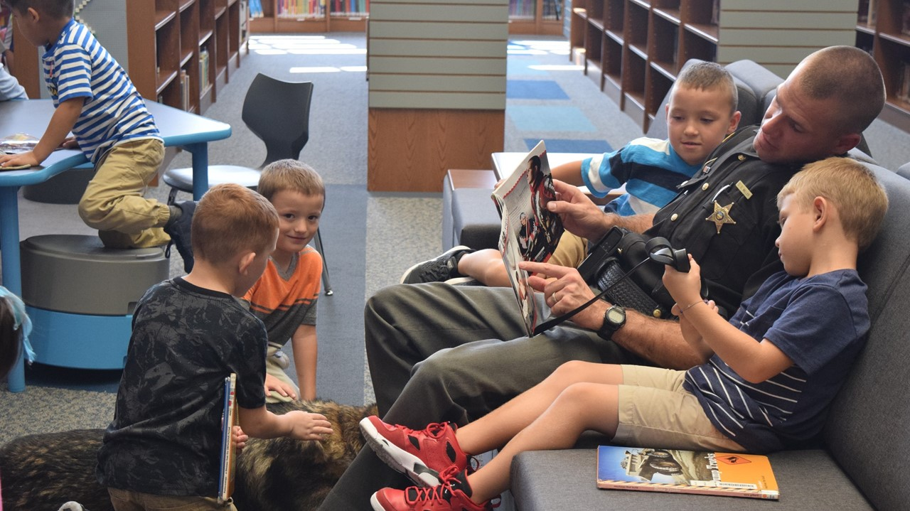 Kindergarten students enjoy petting Cooper and reading with Resource Officer Deputy Miller on the new library furniture.