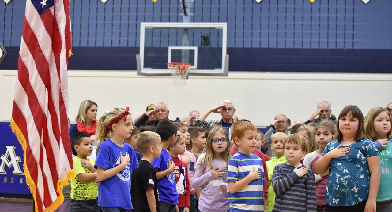 Students and veterans recite the Pledge of Allegiance at the Veterans Day assembly.